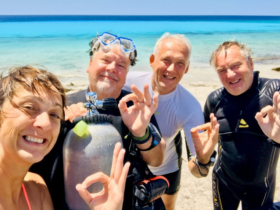 Quatre moniteurs de plongée font le signe OK.