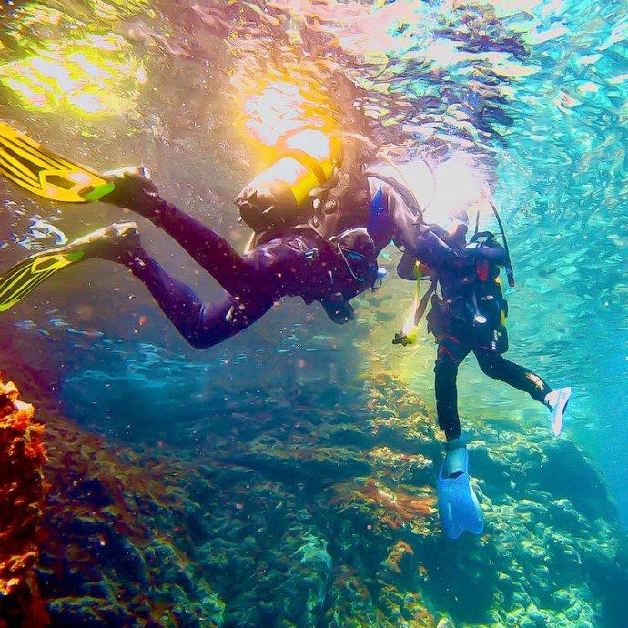 Deux plongeurs dans les eaux d'Espagnes fondent dans les nuances de bleu.