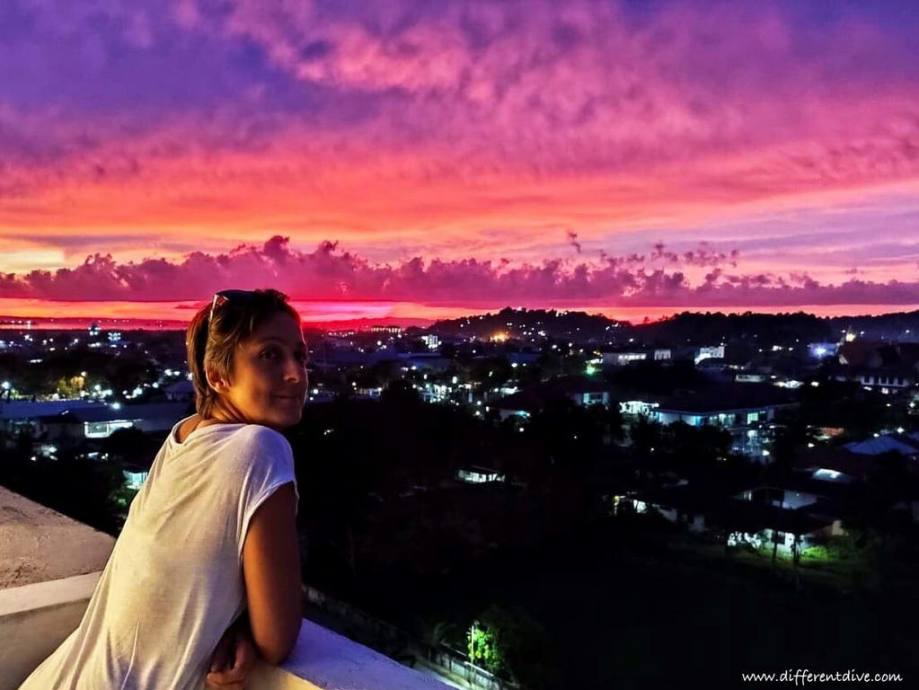 Hélène Adam sur une terrasse de Sorong devant un coucher de soleil.