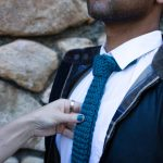 A man is shown from chin down. He is wearing a teal knitted tie, black jacket unzipped, white shirt, and sexy stubble. Another hand holds the tie as if she just finished adjusting it.