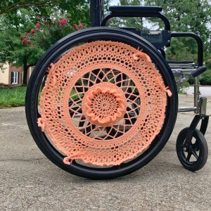 A wheelchair is shown with a bright coral wheel cover. The wheel cover is crocheted by hand with open work and 3D texture