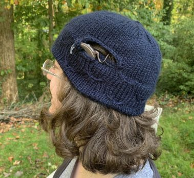 A woman looks off into the woods. She is wearing glasses and a navy blue cochlear implant hat. She has a CI with an earpiece shown in a pocket on the hat and the transmitter is on her scalp under an opening in the hat.