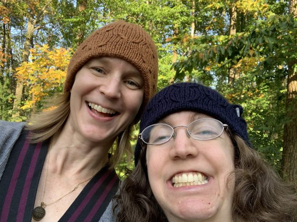 Two woman smile into the camera taking a selfie together. They both wear knit hats. The blond woman wears a burnt orange colored hat with no CI adaptation. The brunette wears a navy hat with a left ear CI adaptation.