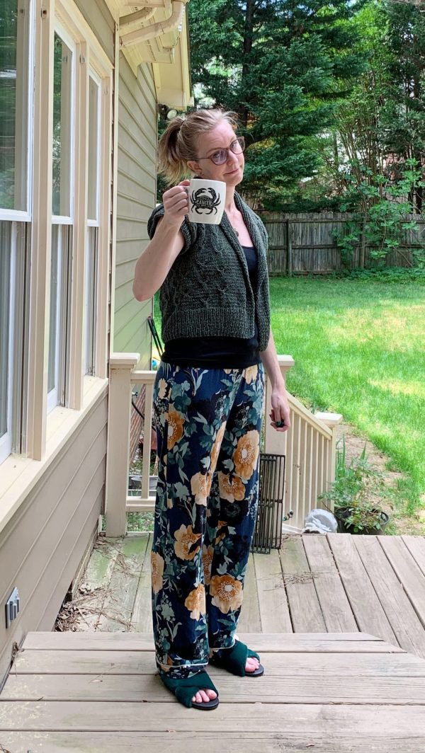 A blond woman is standing on a porch wearing a green knit cardigan, black tank, and pajama pants.