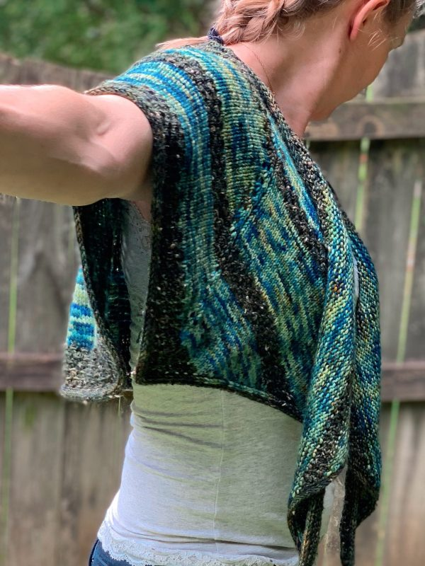 Liz, a blond woman is wearing a blue and green shawl. She is turned to the side so you can see how the shawl is convertible to a shrug.
