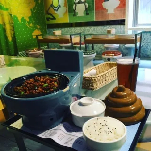Image of food at Modern Toilet themed cafe in Taipei. It shows mince pork and chillis served in a bowl that looks like a toilet with rice that has a poop shaped cover.