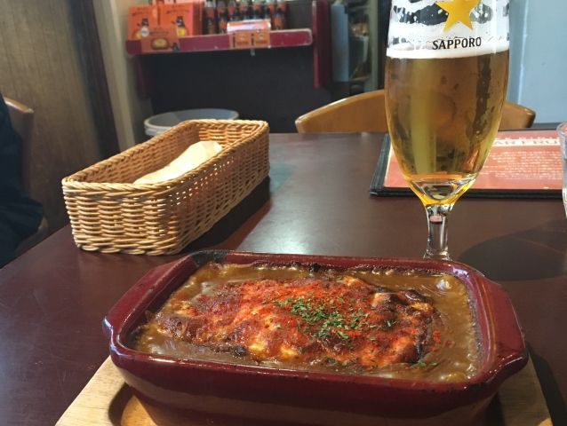 Image shows a dish of Baked Japanese curry - a curry with grilled cheese on top - served in a heavy burgundy dish. Served with a glass of Sapporo beer.