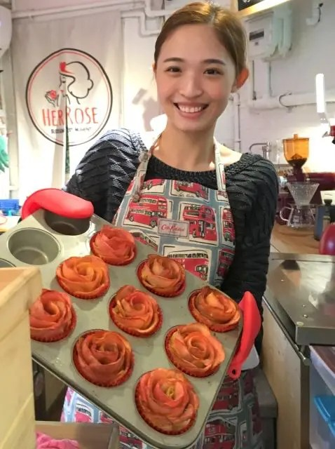 Female baker at the Her Rose cafe in Taipei showing a baking tray of apple cup cakes that look like roses.