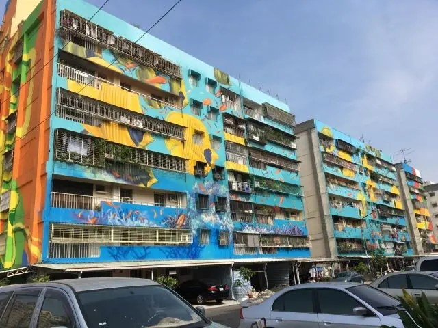 Four huge apartment buildings covered with paintings of fish