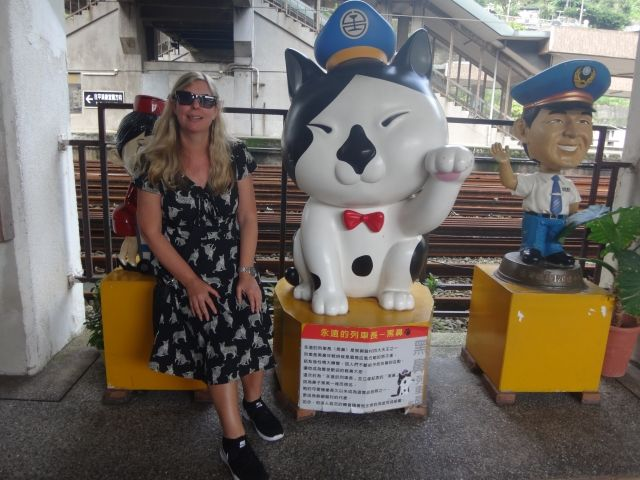 Girl sitting by giant plastic cat