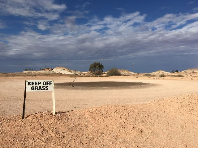 Sandy earth with a Keep of the Grass sign