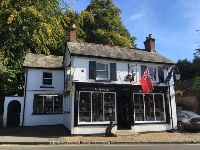 Front of a small white shop with a thatxhed roof called The Coven of Witches in Burley, New Forest