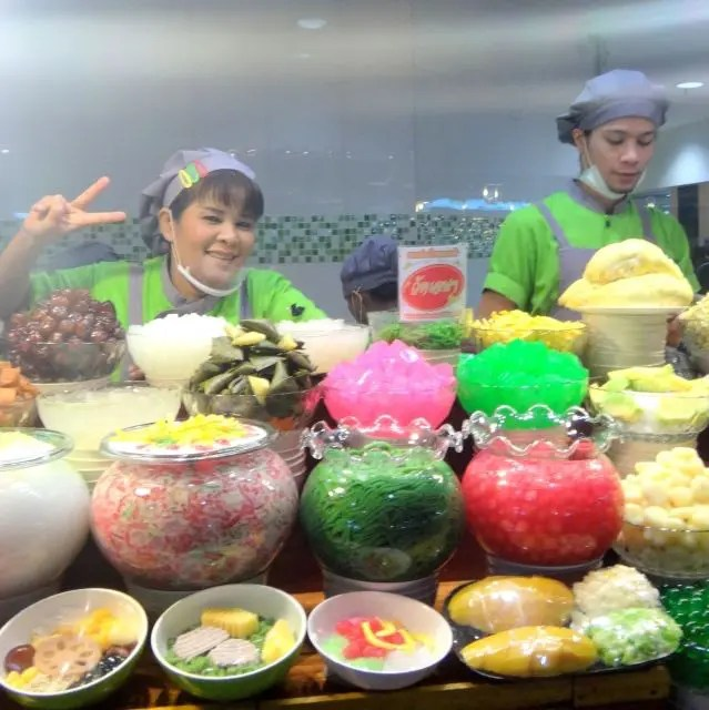 Smiling servers with coloured desserts at MBK Food Island, Bangkok