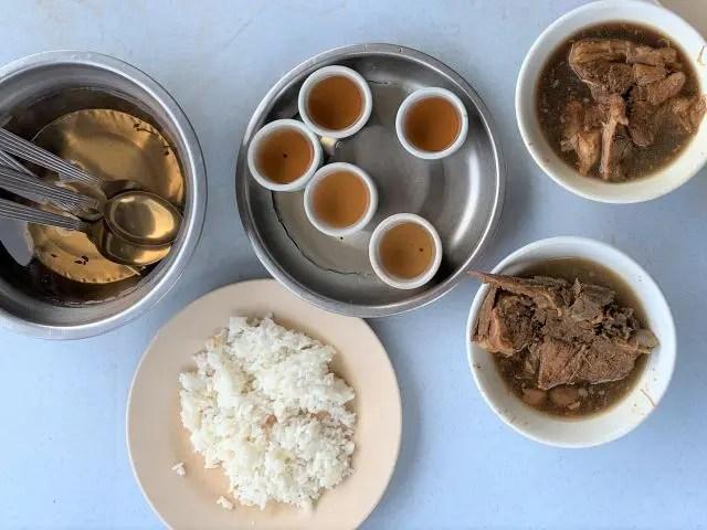 Bowls of Bak Kuh Tek, rice and tea soaking cutlery in Klang, Malaysia