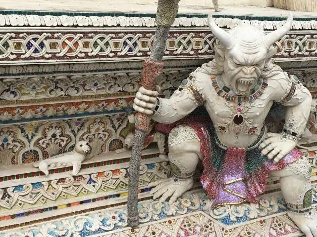 Monster carving with a tiny seal next to it at Wat Pariwat, Bangkok