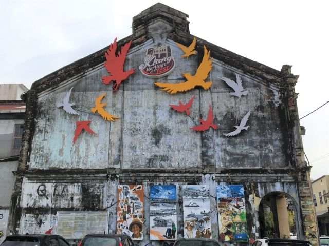 Faded old building in Klang with birds stuck on it.