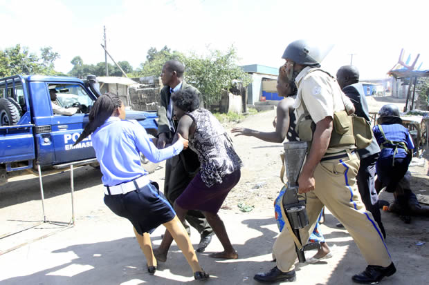 Police officers arrest people found looting in Lusaka's Chaisa Township-picture by Tenson Mkhala