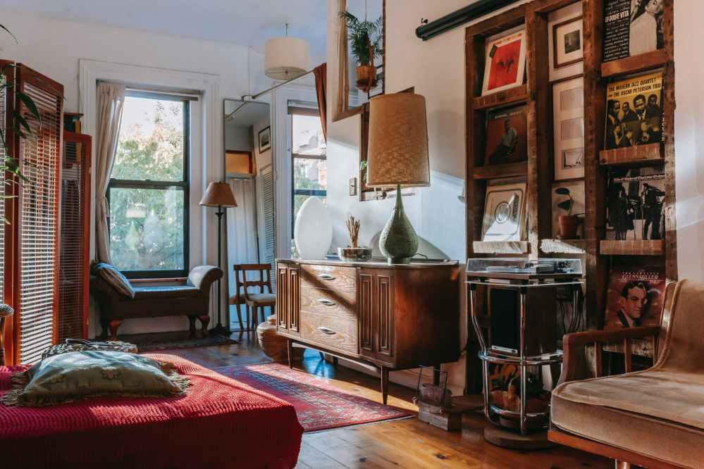 interior of cozy studio with bed and couch decorated with vintage furniture and vinyl records