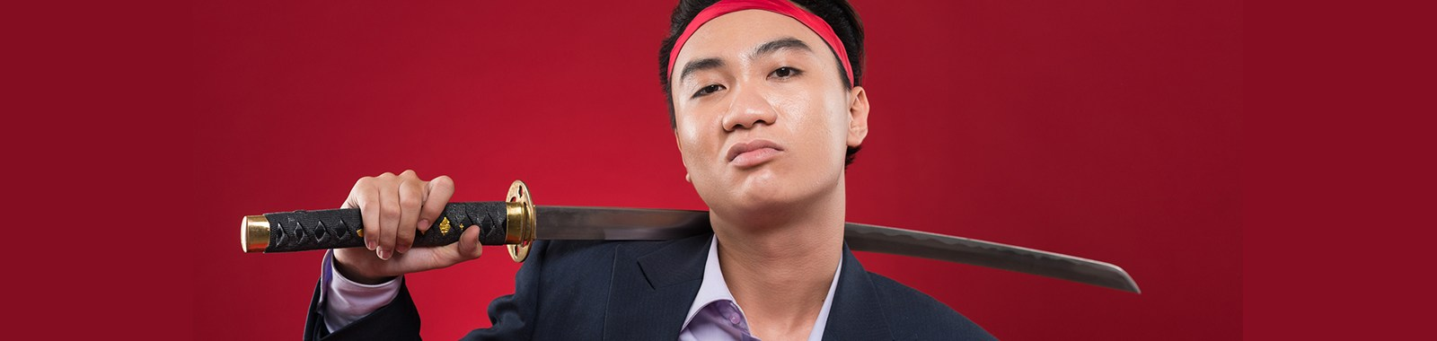 Portrait of confident Vietnamese manager with katana over his shoulder
