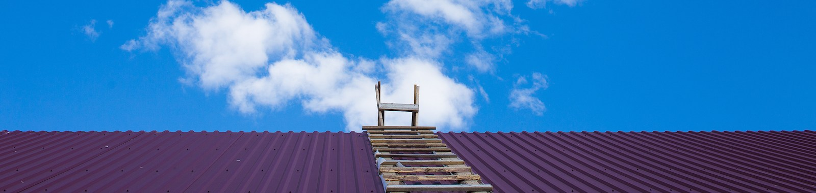 wooden ladders are on both sides of the iron roof. beautiful blue sky with clouds.the concept of achievement and competition. copy space for your text