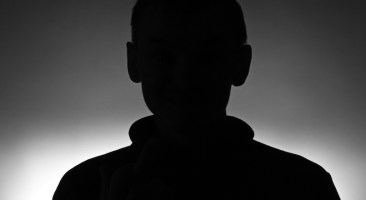 Silhouette of young man in pullover on dark background