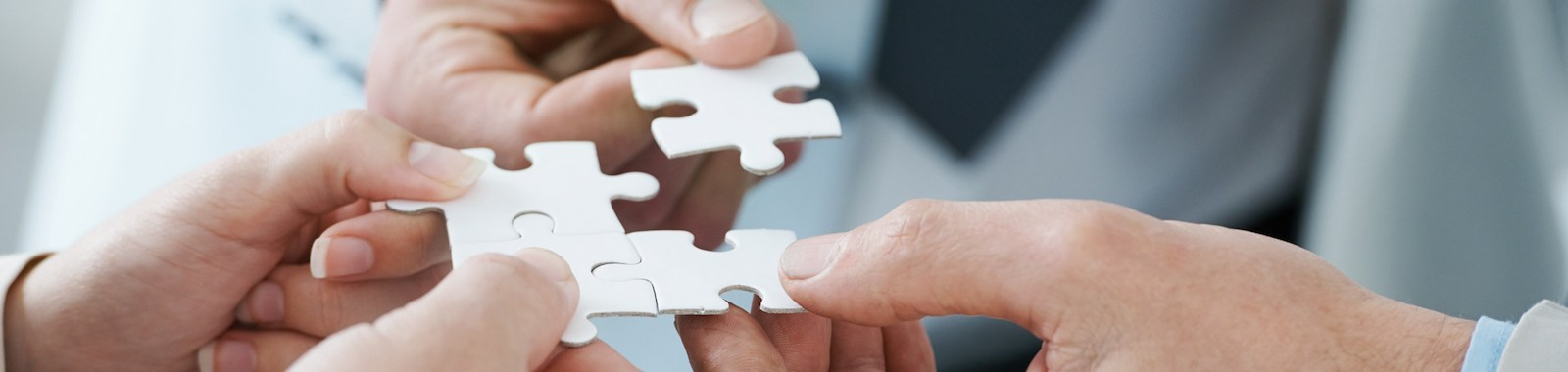 A business concept image of puzzle pieces fitting together - closeup