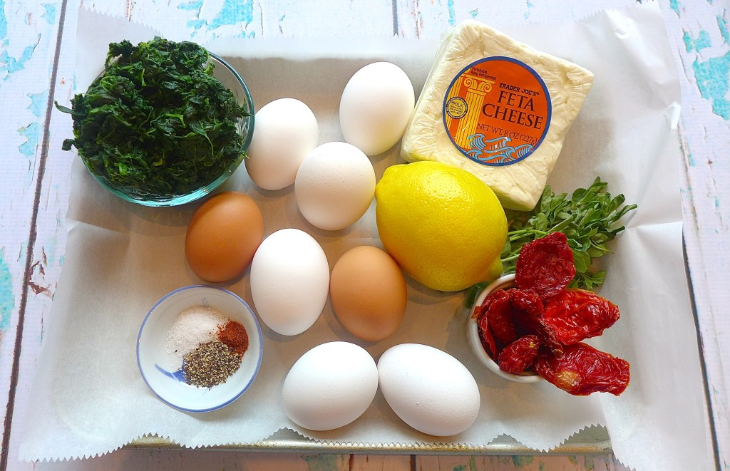 Ingredients for frittata muffins: eggs, spinach, sundried tomatoes, feta cheese, lemon, oregano, salt, pepper and cayenne.
