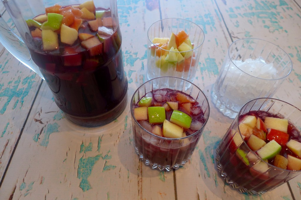 Finally, fill each glass with ice and fruit. Add the remaining fruit to the pitcher. Set out spoons, napkins and extra simple syrup. Dig in to Ruby Red Sangria and let the celebrations begin!