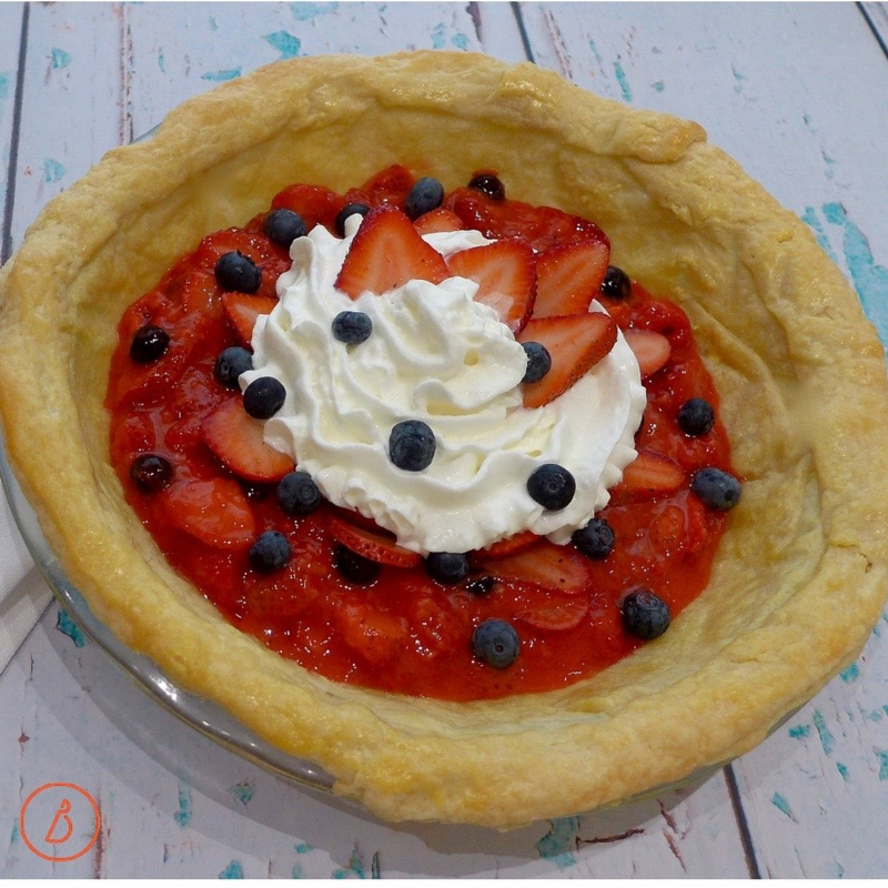 Berry pie topped with whipped cream and sliced extra strawberries.