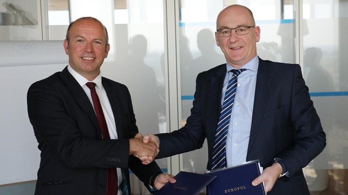 Kevin Brown and Steven Wilson shaking hands at Europol headquarters