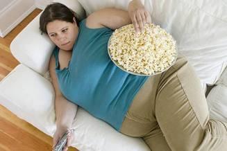 Wanita dengan berat badan berlebih sedang ngemil.