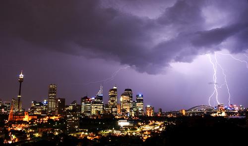 高層ビル群の夜景と橋、稲妻、立ち込める雷雲