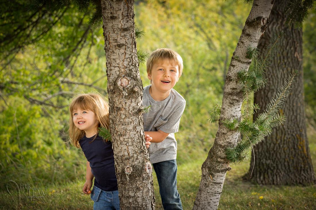 Crianças brincando de esconde-esconde em volta da árvore.