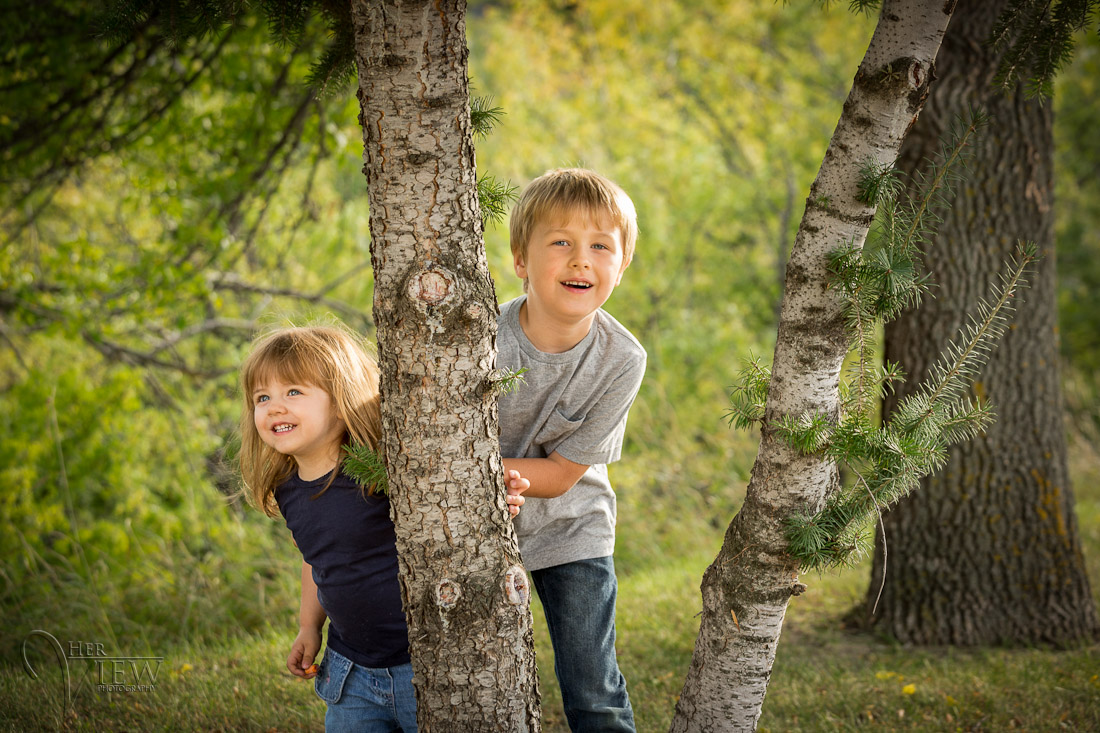 Kids playing a game of peek-a-boo around the tree