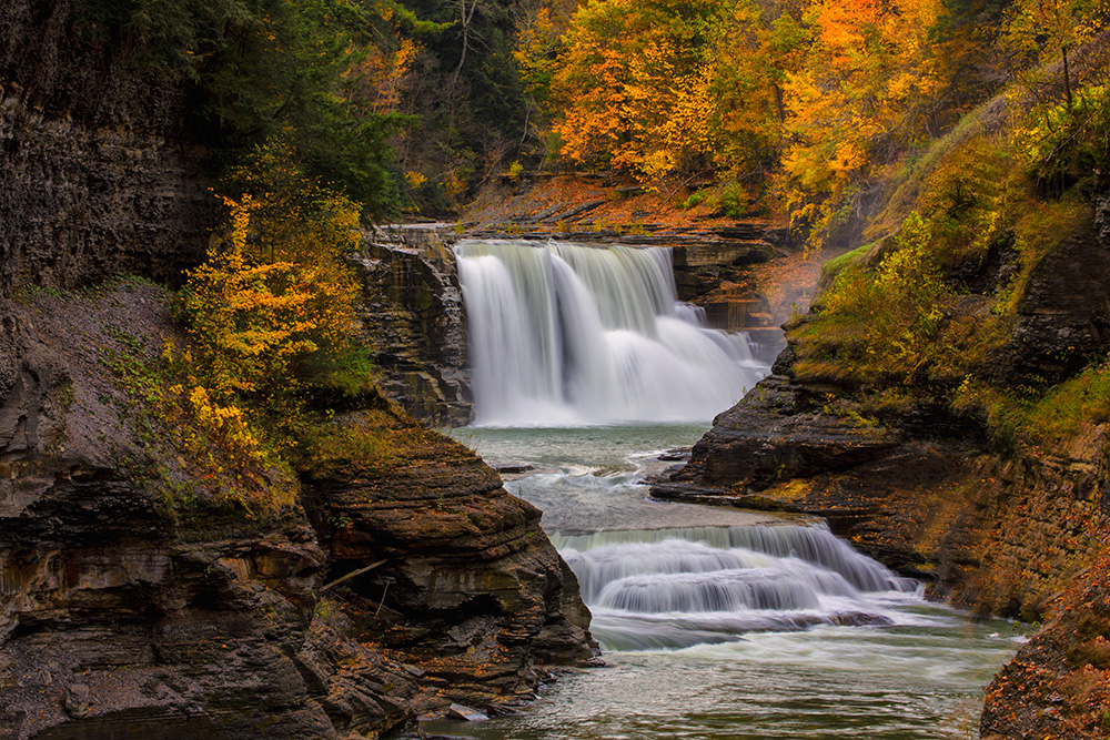 """For this image of Lower Falls in Letchworth State Park in New York, I knew I wanted a creamy look to the falls.  They were flowing well so I knew a moderately slow shutter speed would give me what I wanted.  I also knew as I composed it that I wanted the falls framed by some of the gorgeous colors of the fall foliage.  I set my exposure based on two things- I wanted a slow shutter speed and I wanted deep depth of field. EOS 5D Mark III, EF 70-300 f/4-5.6L, ISO 100, f/25, .3""""."""