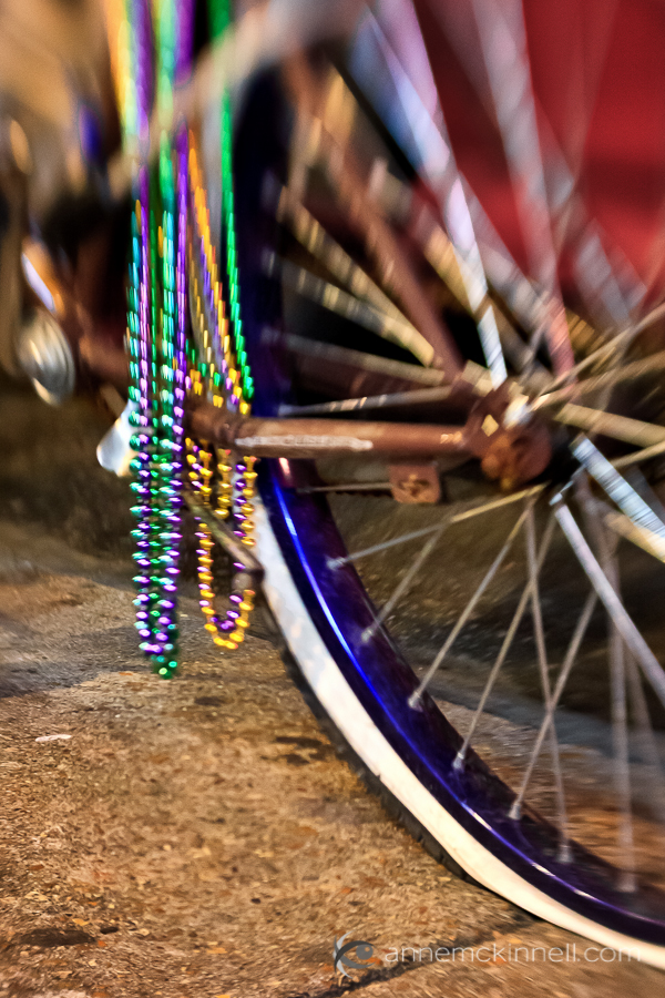 photography rut and motivation Bicycle with flat tire and Mardi Gras beads in New Orleans, by Anne McKinnell.