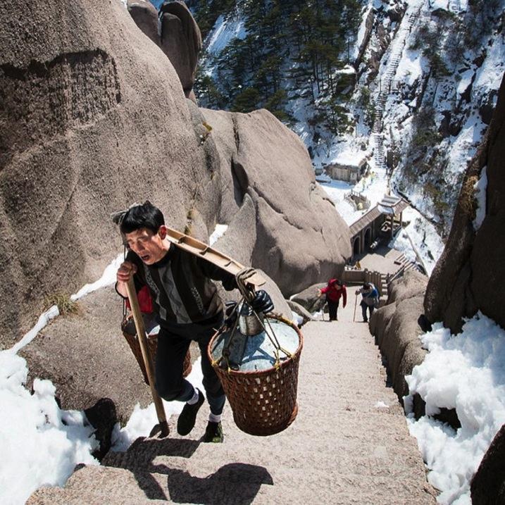 person climbing a mountain with buckets