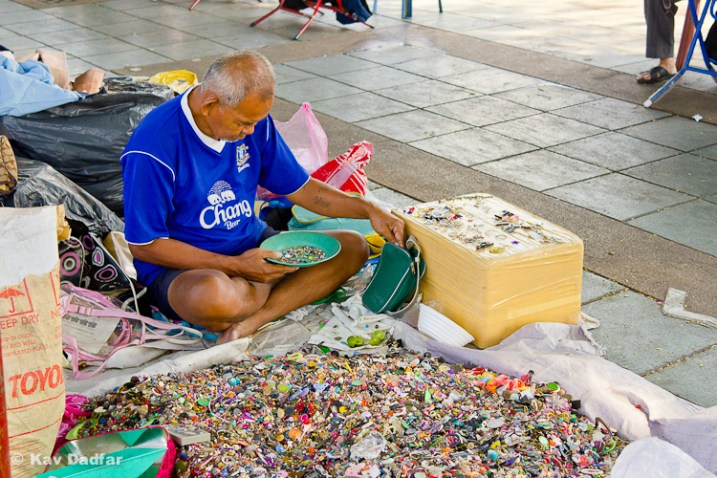 Man selling buttons in a market by the side of the road in Bangkok.