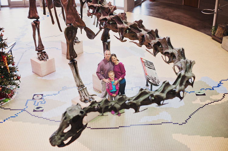 family posing near a dinosaur