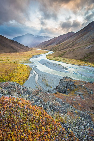 The autumn colors in the close foreground provide a good starting place for this image, guiding the eye to the winding river and then onto the stormy mountains beyond.