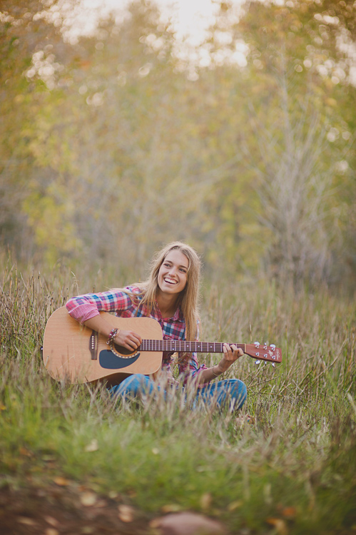 portrait of a musician in the grass playing guitar