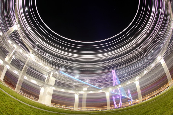 A bridge in Busan is photographed using a fish-eye lens in conjunction with kinetic light painting. A shallower angle was used here, perhaps around 45 degrees.
