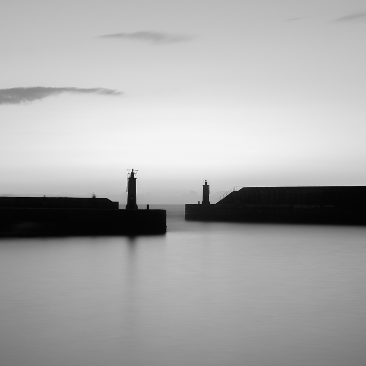lighthouses out at sea in black and white