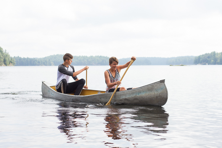 Two boys canoeing, in a photo taken to capture the mood and atmosphere of the shot.