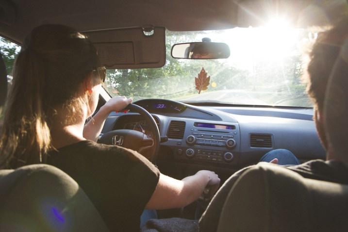 A warm, summery picture of a couple driving a car - capture the mood and atmosphere of the shot.