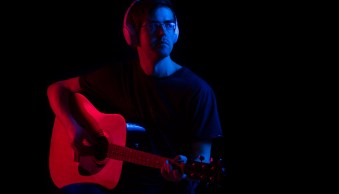 A man holding a guitar, lit by light from blue and red off camera flashes