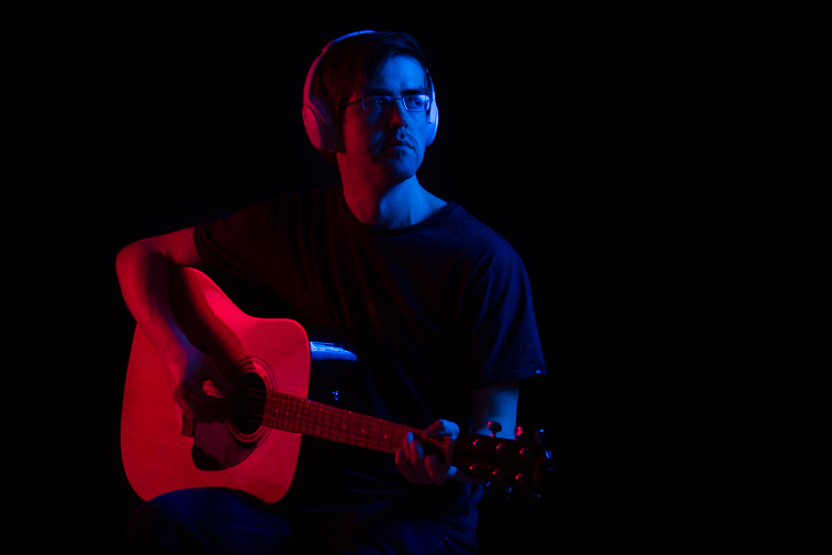 A man holding a guitar, lit by light from blue and red colored gels on off-camera flashes