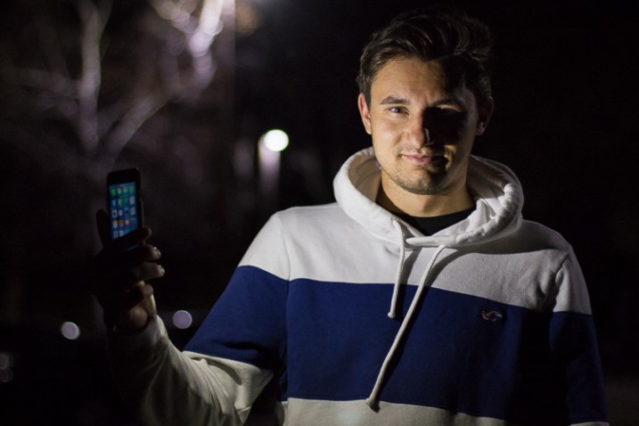 A photo of a man lit by one camera flashlight as the key light - How to Use a Cell Phone for Dramatic Night Photography