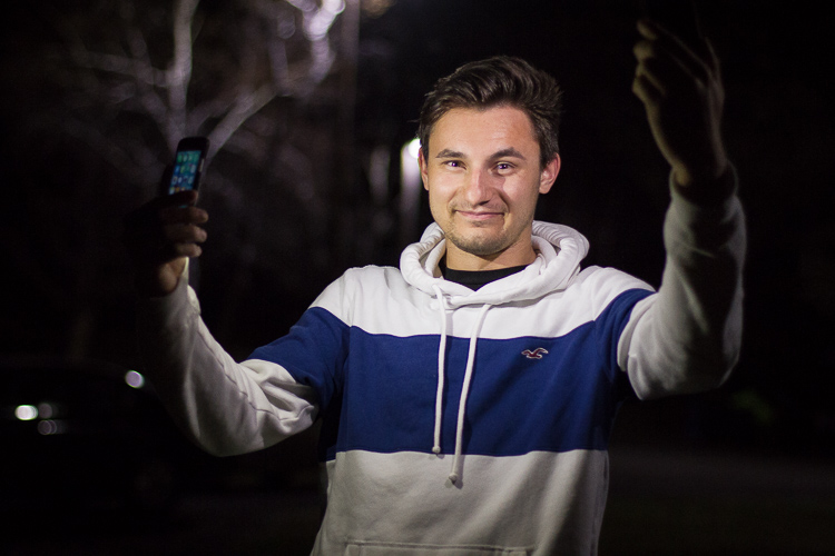 A portrait of a man lit by two cell phone flashlights he is holding in his hand