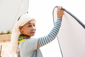 Pwo Karen woman holding up a photographic reflector during a portrait session
